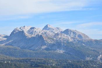 Kser je manj izrazit vrh nad Spodnjo Komno. Na fotografiji se vidijo osrednje Julijske Alpe s Triglavom in gorami, ki ga obdajajo.